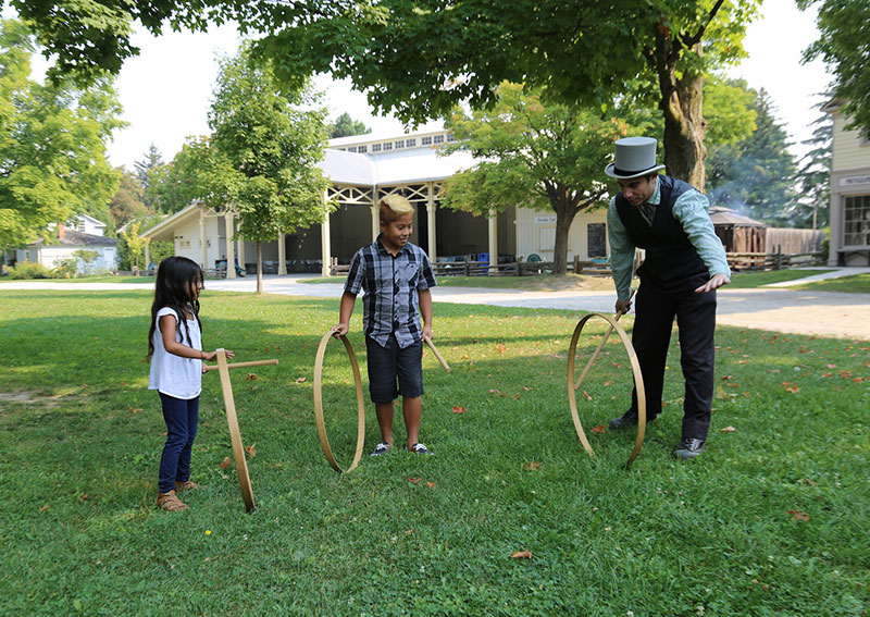 A pioneer man and two children playing hoops