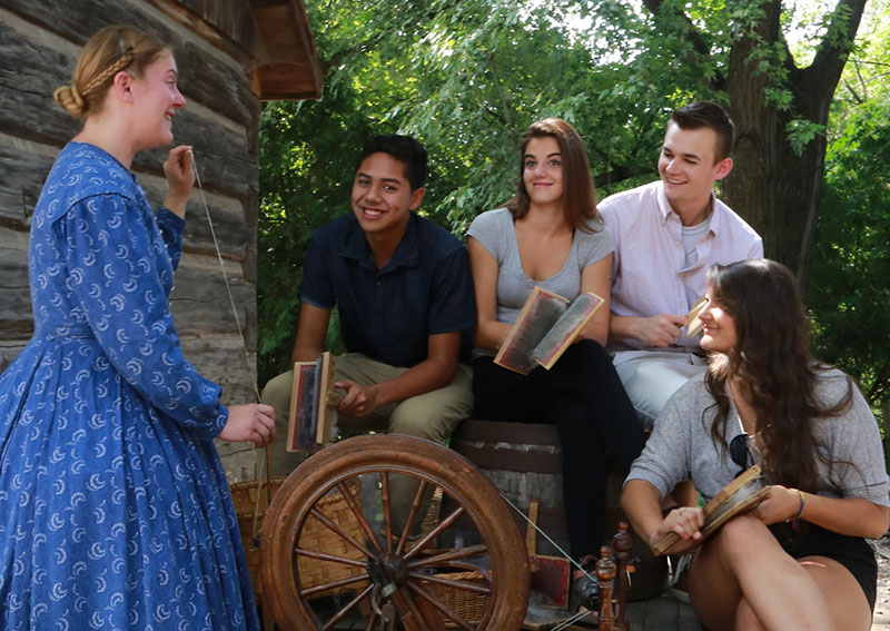 A group of young people with a pioneer woman spinning yarn
