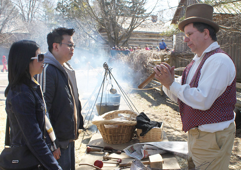A pioneer man showing two people old tools