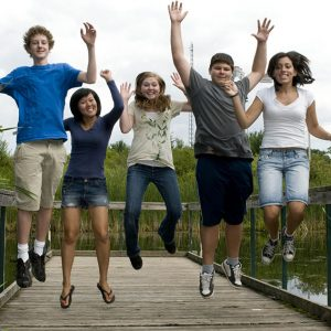 A group of teenagers jumping in the air on a dock in a wetland