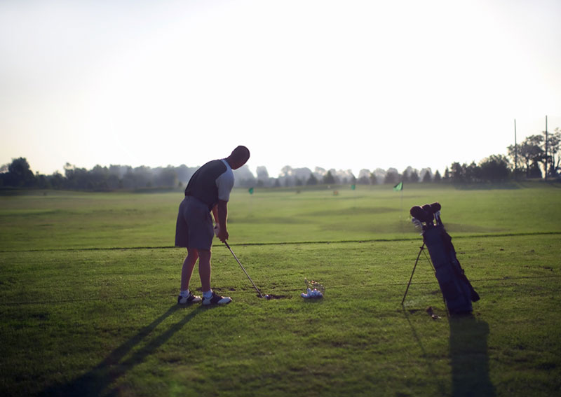 A golfer at a driving range hitting a golf ball