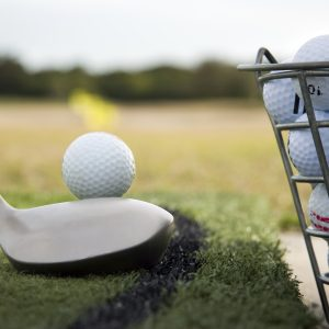 A golf ball, golf club and bucket of golf balls