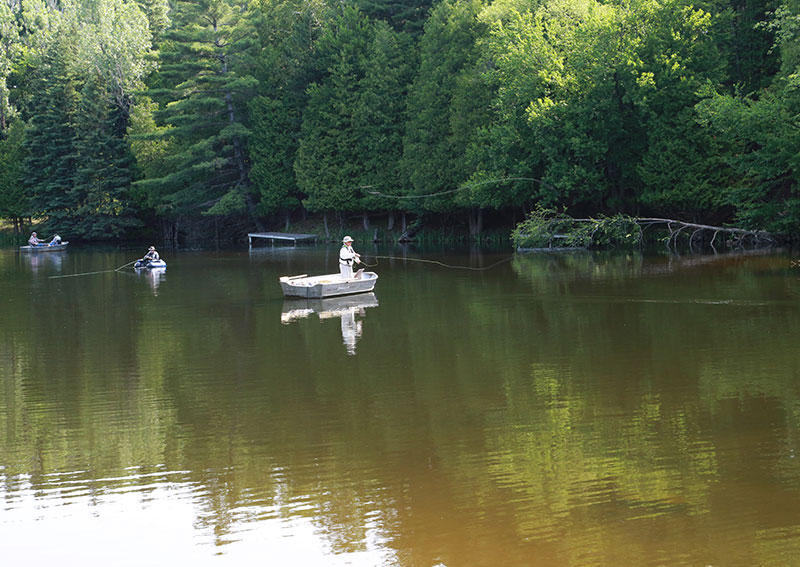 People fly fishing from boats on a pond